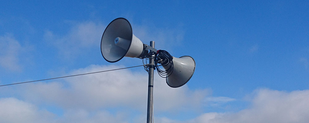 A couple of horn speakers as part of a large announcement system.